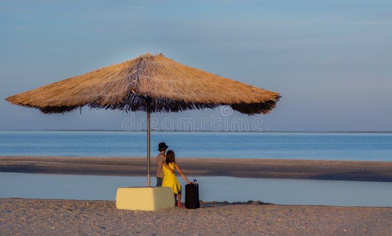Un ragazzo in un cappello e una ragazza sulla spiaggia con una valigia sotto un ombrello della paglia esaminano la distanza Viagg immagine stock libera da diritti