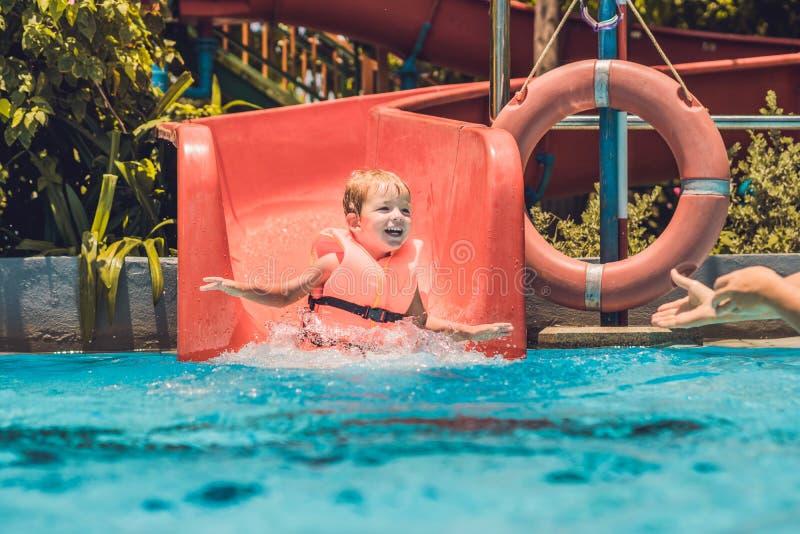 Un ragazzo in un giubbotto di salvataggio fa scorrere giù da uno scorrevole in un parco dell'acqua fotografia stock