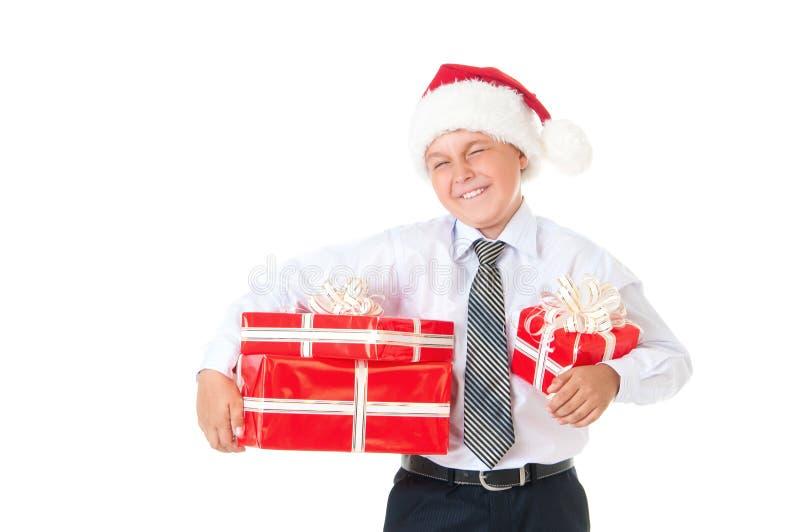Un ragazzo in una camicia bianca ed in un cappello di Santa Claus del nuovo anno con i regali rossi Fondo bianco isolato fotografia stock
