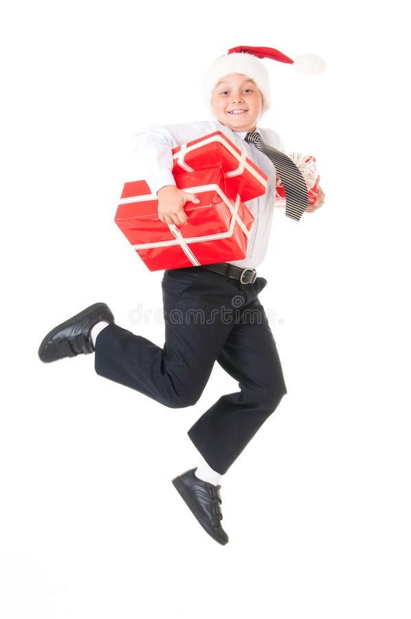 Un ragazzo in una camicia bianca ed in un cappello di Santa Claus del nuovo anno sta saltando con i regali rossi Fondo bianco iso immagini stock