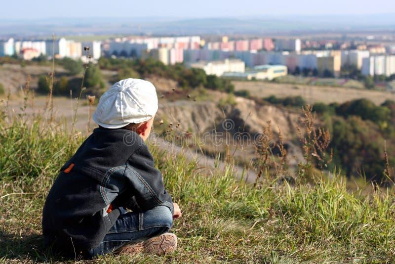 Un ragazzo in una protezione bianca sta osservando sulla città immagini stock libere da diritti
