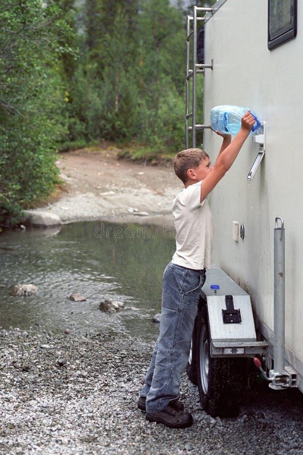 Un ragazzo versa l'acqua in un campeggiatore da un fiume della foresta da una bottiglia di cinque-litro fotografie stock