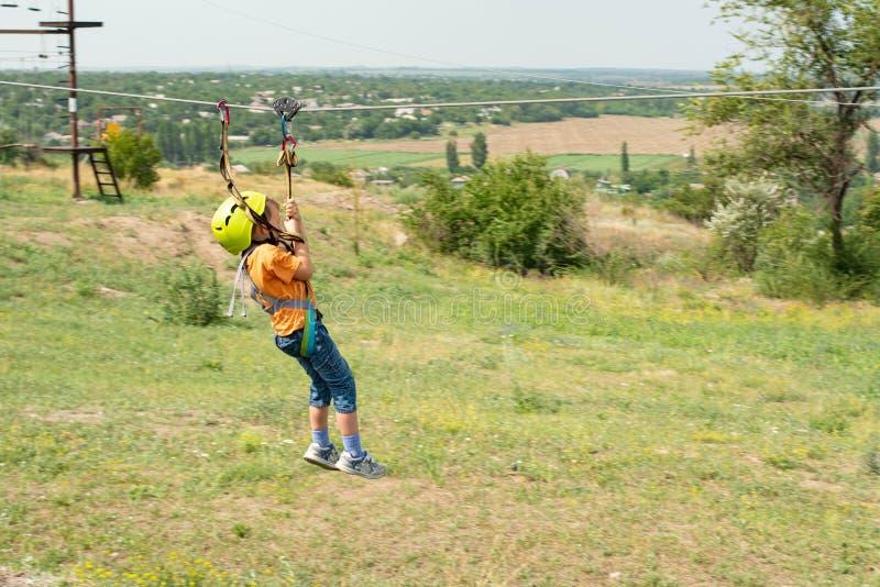 Un ragazzo vestito in un casco ed in un'assicurazione protettivi, scende la corda, discende tenendo un cavo protettivo fotografia stock libera da diritti