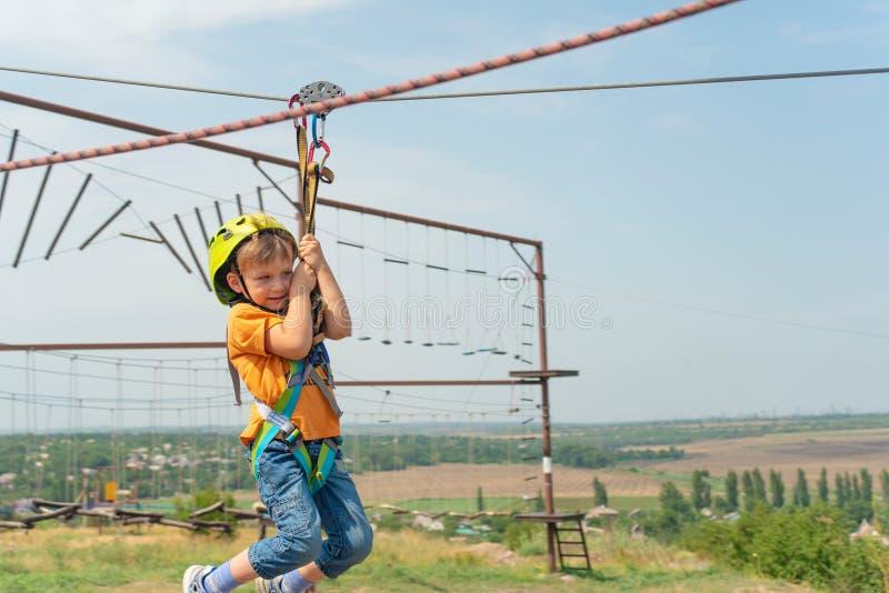 Un ragazzo vestito in un casco ed in un'assicurazione protettivi, scende la corda, discende tenendo un cavo protettivo immagine stock libera da diritti