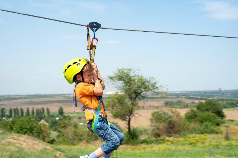 Un ragazzo vestito in un casco ed in un'assicurazione protettivi, scende la corda, discende tenendo un cavo protettivo fotografia stock