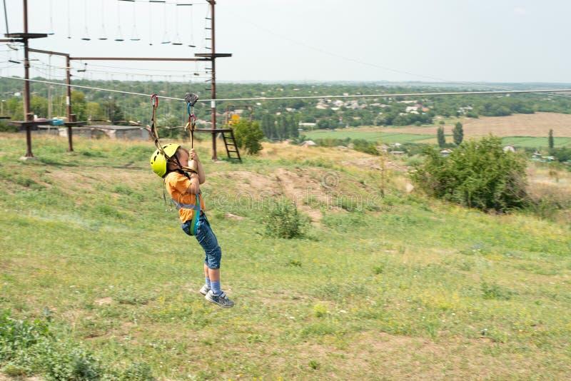 Un ragazzo vestito in un casco ed in un'assicurazione protettivi, scende la corda, discende tenendo un cavo protettivo immagini stock