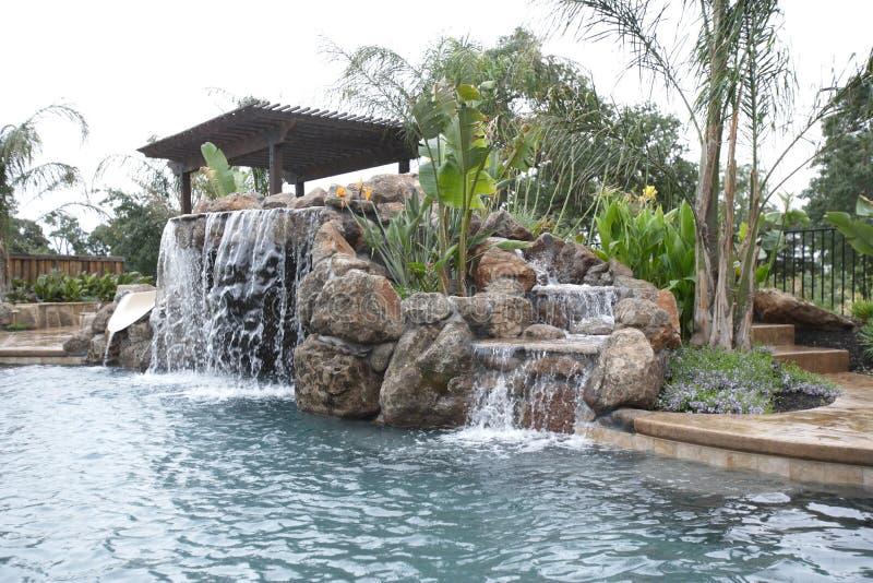 Un raggruppamento con una cascata in un cortile di lusso immagini stock