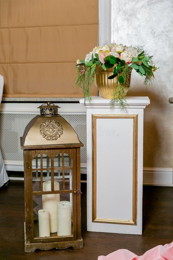 Un ramo blanco de peonías, de hortensia y de Anthurium en una maceta del oro en un pilar blanco en un estilo clásico Linterna de  fotos de archivo