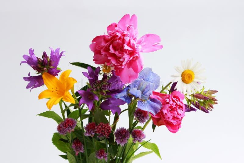 un ramo de diversas flores salvajes del campo y del jardín: manzanilla, campana, lirio, cebolletas, iris, peonía fotos de archivo