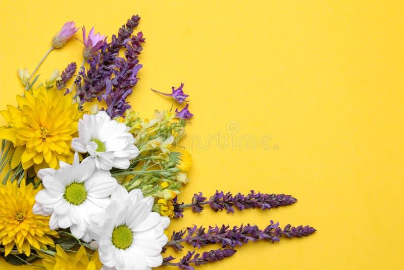 Un ramo de diversos wildflowers en un fondo amarillo de moda brillante con un lugar para la inscripción imágenes de archivo libres de regalías