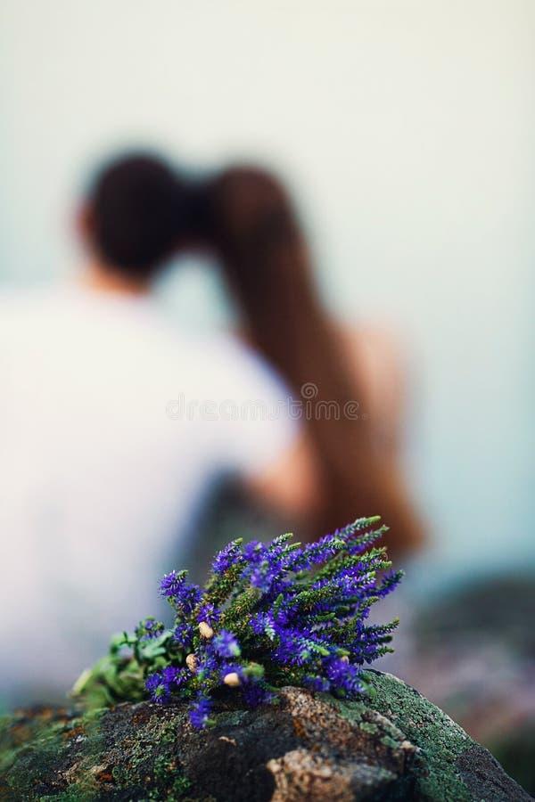 Un ramo de flores azules del campo con los caracoles miente en una roca en naturaleza, y detrás de sentar un par cariñoso y abraz fotos de archivo libres de regalías