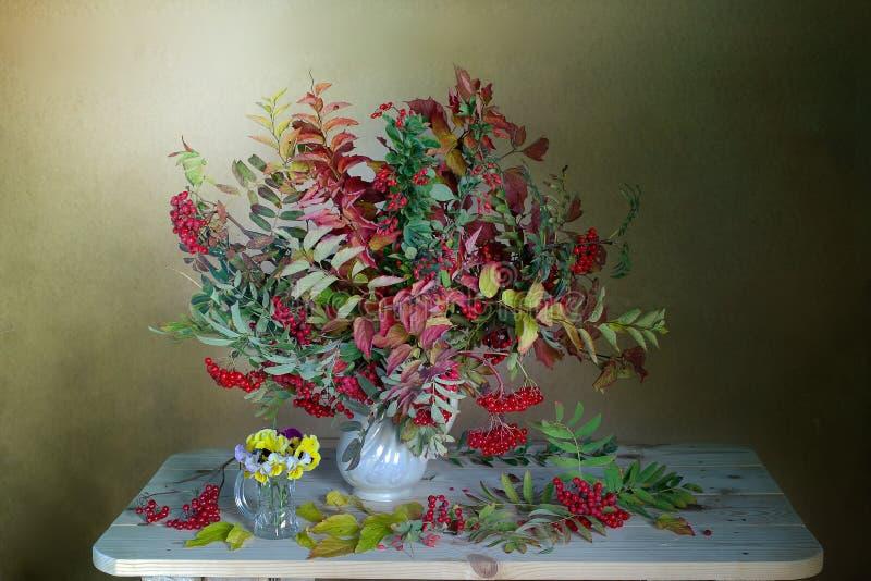 Un ramo de hojas coloridas y de bayas rojas en otoño Aún-vida del otoño con el pasto hermoso del otoño fotografía de archivo