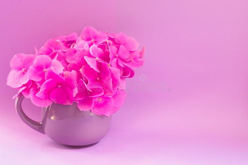 Un ramo de hortensias rosadas en una pequeña taza de la lila en un fondo de la lila foto de archivo libre de regalías