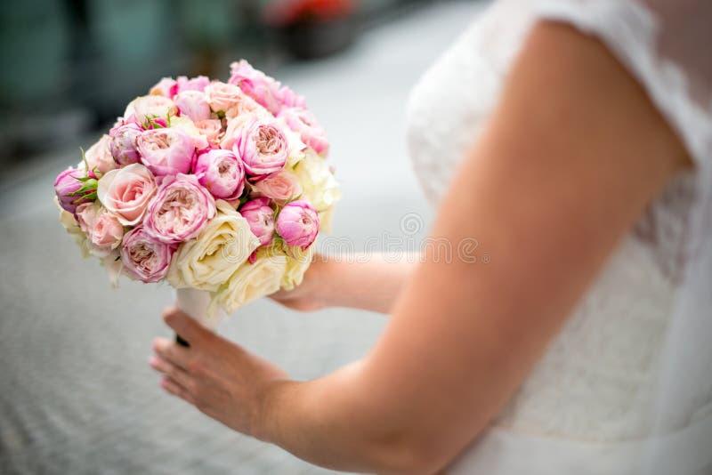 Un ramo de la boda de rosas y de peonías en las manos de la novia Primer En un fondo borroso fotografía de archivo libre de regalías
