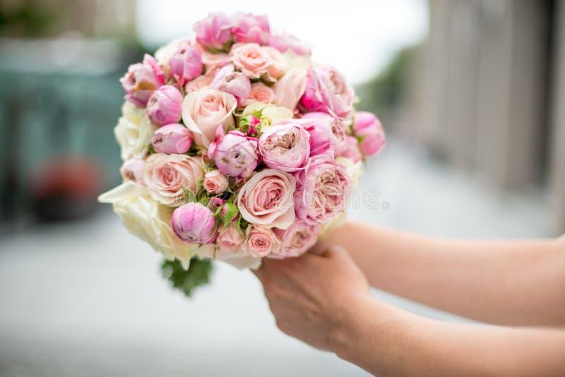 Un ramo de la boda de rosas y de peonías en las manos de la novia Primer En un fondo borroso fotos de archivo