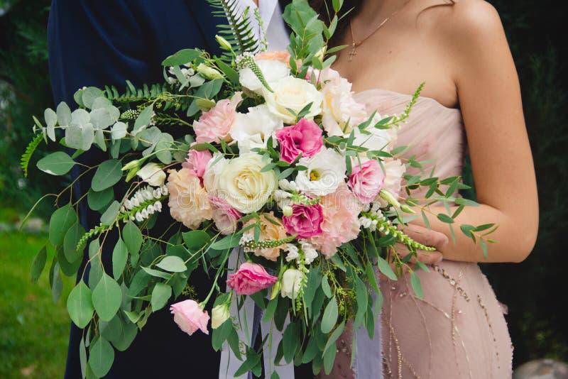 Un ramo de la boda se sostiene en las manos de los recienes casados fotografía de archivo