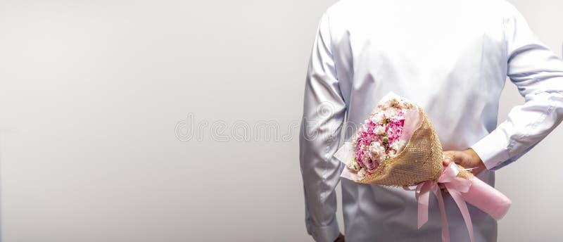 Un ramo de la flor de la tenencia del hombre detrás de su parte posterior en el fondo blanco fotos de archivo