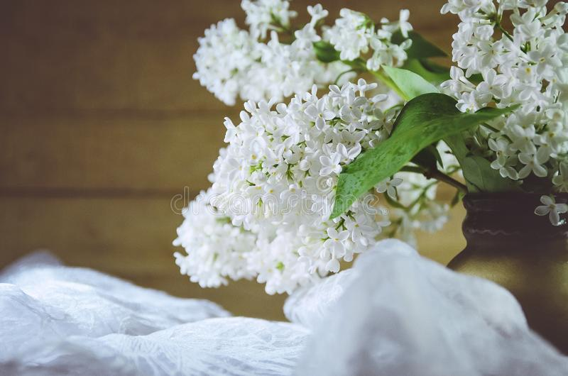 Un ramo de lila blanca en un pote de arcilla en un fondo de madera primer, foco suave fotografía de archivo