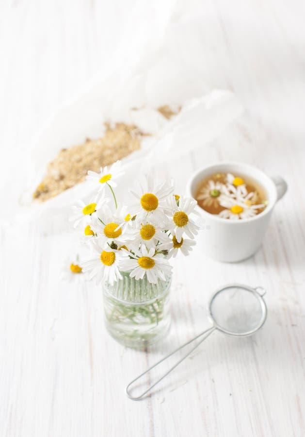 Un ramo de margaritas y de caldo en una taza en una tabla blanca imagenes de archivo