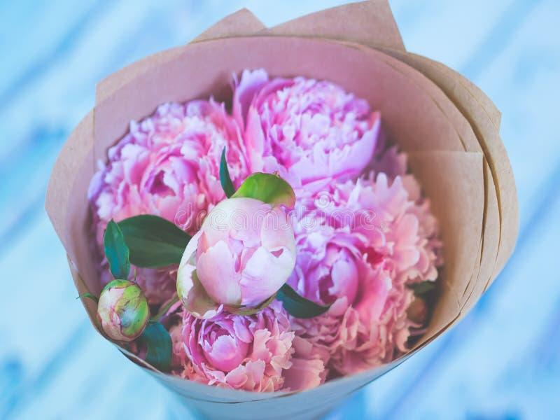 Un ramo de peonías rosadas hermosas en una tabla de madera azulada contra fondo suave-enfocado imagen de archivo libre de regalías