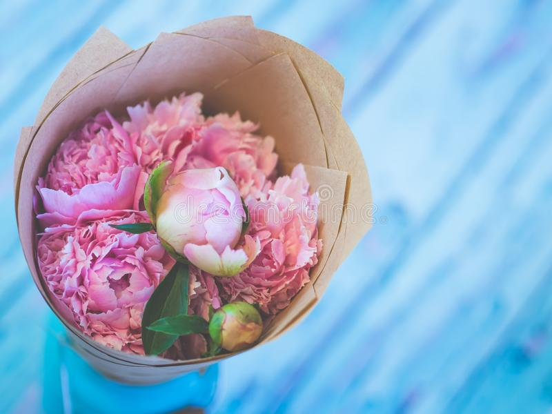 Un ramo de peonías rosadas hermosas en una tabla de madera azulada contra fondo suave-enfocado foto de archivo