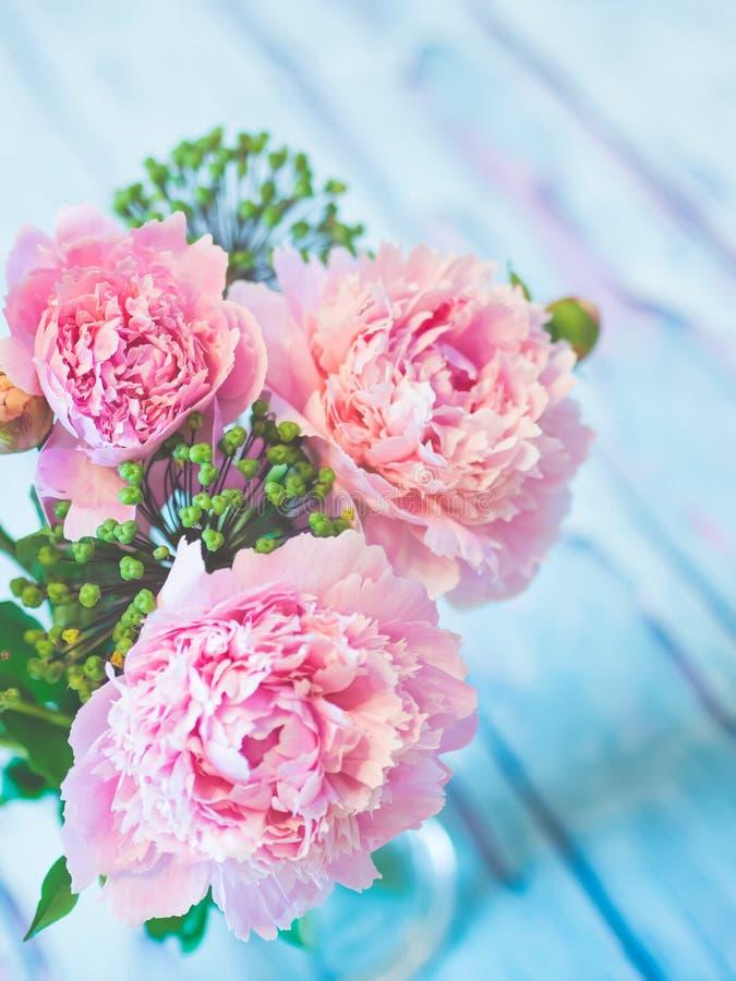 Un ramo de peonías rosadas hermosas en una tabla de madera azulada contra fondo suave-enfocado fotografía de archivo