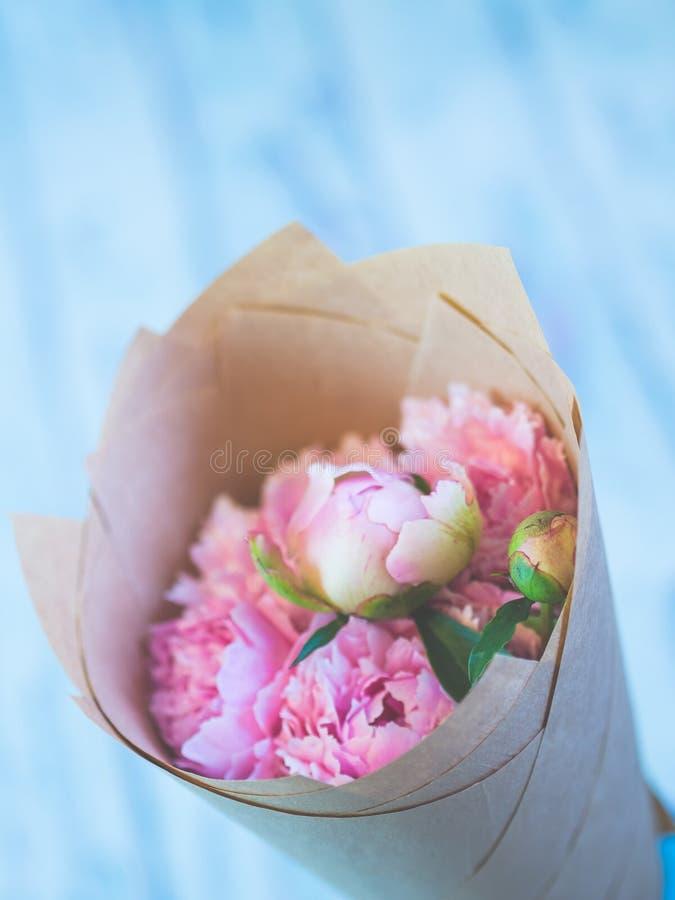 Un ramo de peonías rosadas hermosas en una tabla de madera azulada contra fondo suave-enfocado fotos de archivo
