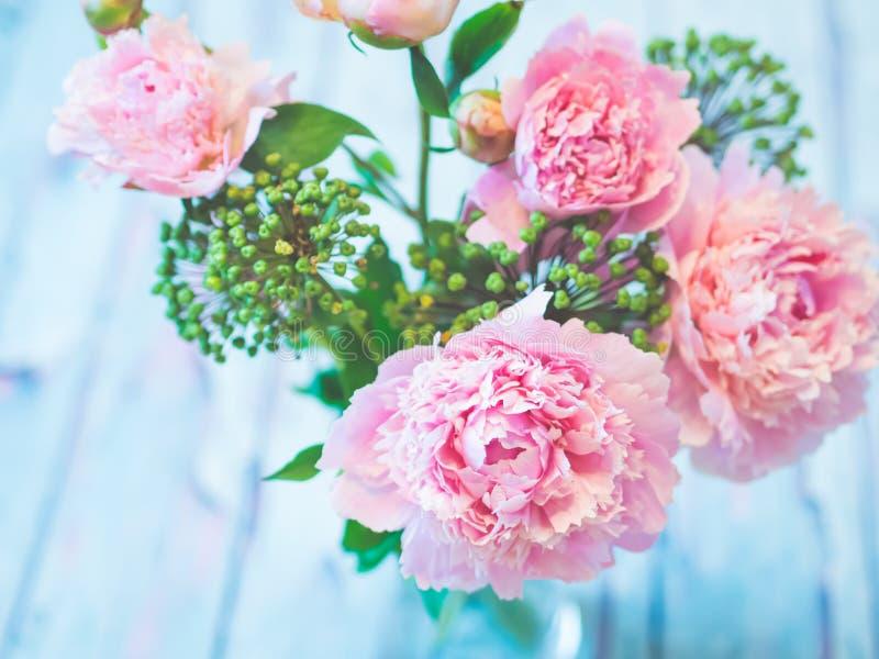 Un ramo de peonías rosadas hermosas en una tabla de madera azulada contra fondo suave-enfocado imágenes de archivo libres de regalías