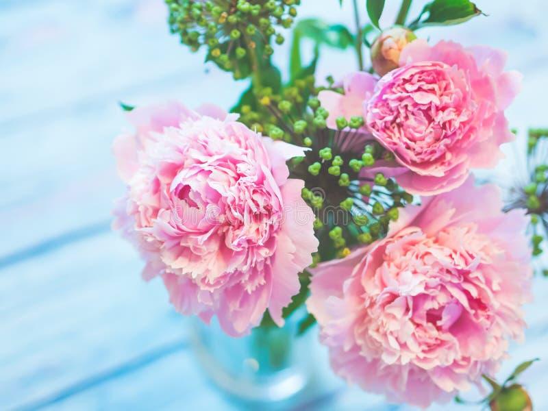Un ramo de peonías rosadas hermosas en una tabla de madera azulada contra fondo suave-enfocado imagen de archivo