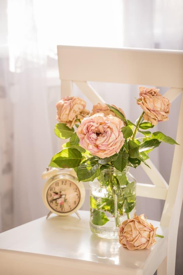Un ramo de rosas cremosas marchitadas en una silla blanca en el interior imagen de archivo