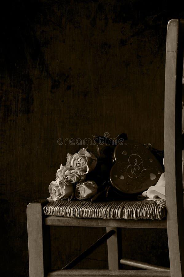 Un ramo de rosas rosadas y de una caja bajo la forma de corazón con los dulces imagenes de archivo