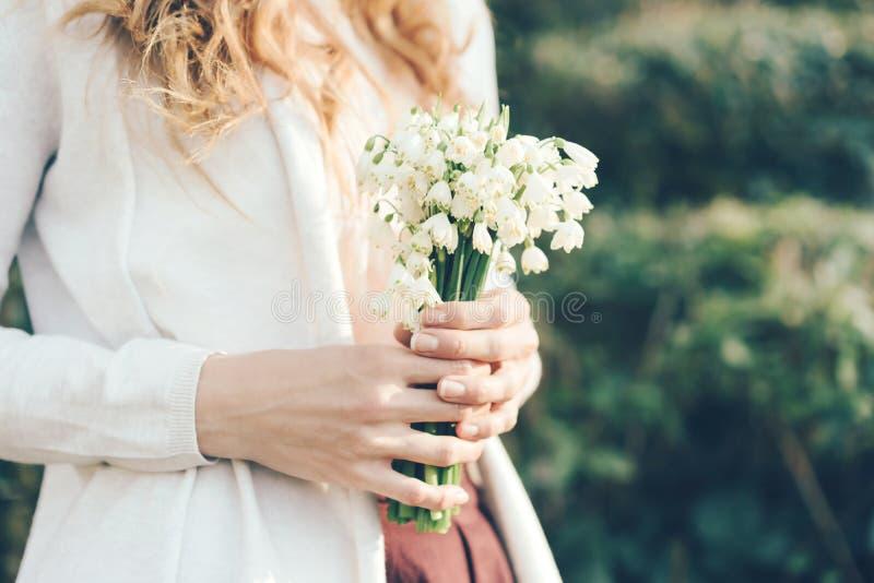Un ramo de snowdrops en las manos de una mujer al aire libre foto de archivo libre de regalías