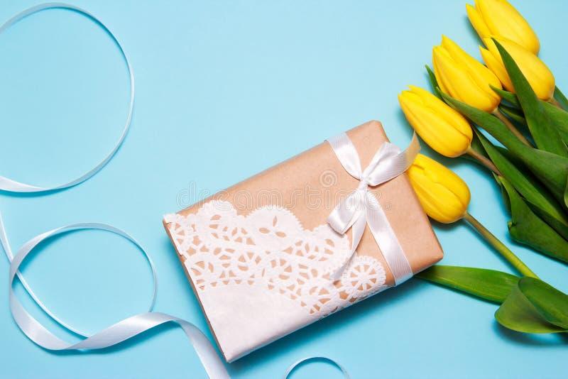Un ramo de tulipanes amarillos y de un regalo del papel del arte adornado con una servilleta del cordón en un fondo de papel azul imagenes de archivo