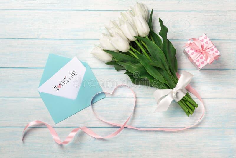 Un ramo de tulipanes blancos y una cinta rosada bajo la forma de corazón con una caja de regalo, una nota del amor y un sobre del fotos de archivo