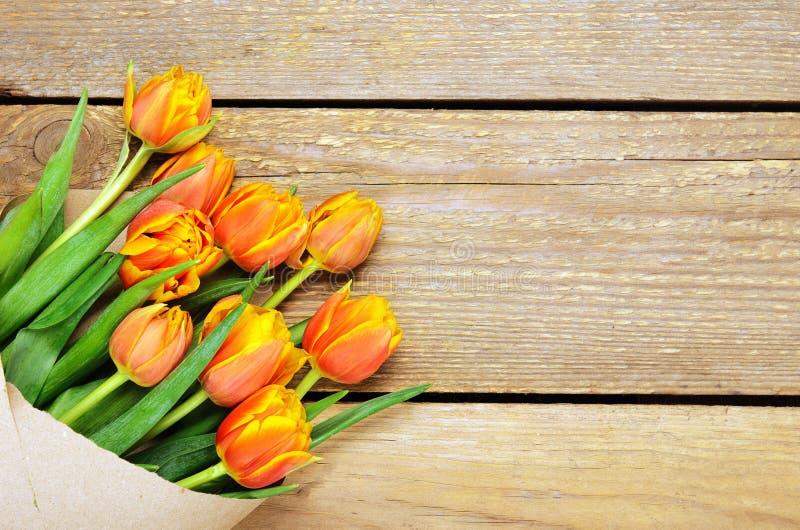 Un ramo de tulipanes rojo-amarillos en Kraft que empaqueta en un fondo de madera Copie el espacio, visión superior, endecha del p imagenes de archivo