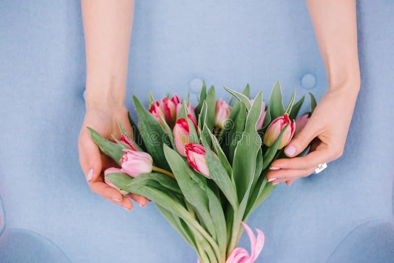 Un ramo de tulipanes rojos que la muchacha abraza sus manos en un gentl imagen de archivo