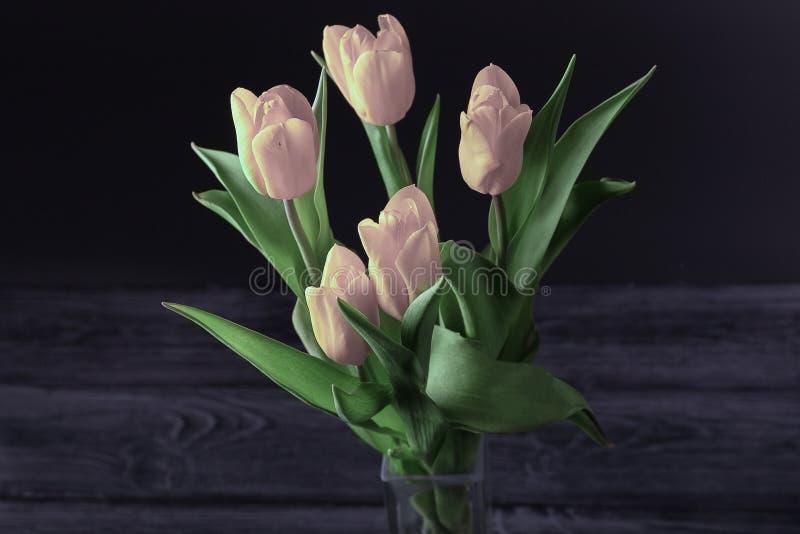 Un ramo de tulipanes rosados en un fondo oscuro, visión superior foto de archivo