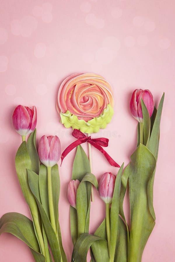 Un ramo de tulipanes y de merengue del caramelo en un fondo rosado fotos de archivo