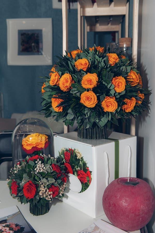 Un ramo enorme de rosas anaranjadas hermosas adornadas en el interior en una mesita de noche blanca imagen de archivo libre de regalías