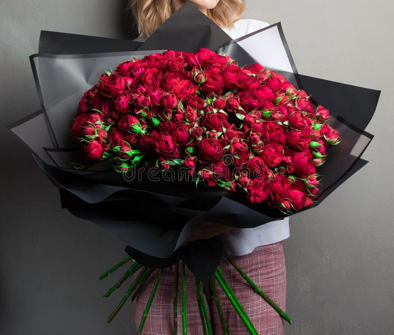 Un ramo enorme grande de rosas y de brotes rojos del jard?n en el papel de embalaje negro, un elegante imagen de archivo