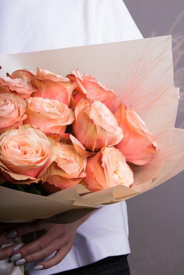 Un ramo hermoso de flores de los colores de las rosas, de color salm?n y anaranjados, en las manos de una muchacha en papel del o foto de archivo libre de regalías