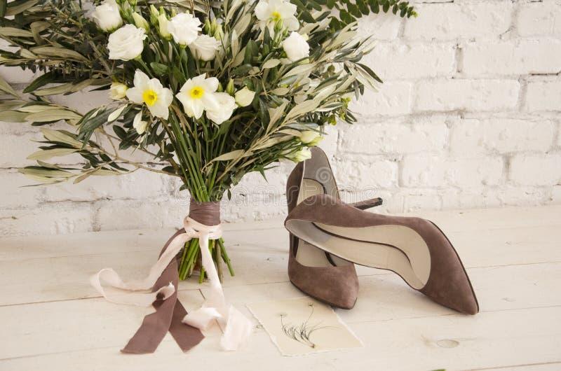 Un ramo hermoso de flores y de zapatos imágenes de archivo libres de regalías