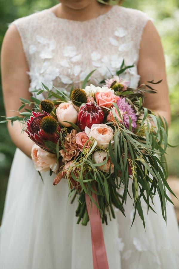 Un ramo hermoso de la boda con el eucalipto, las rosas y las flores exóticas en las manos de la novia en un vestido de boda imágenes de archivo libres de regalías