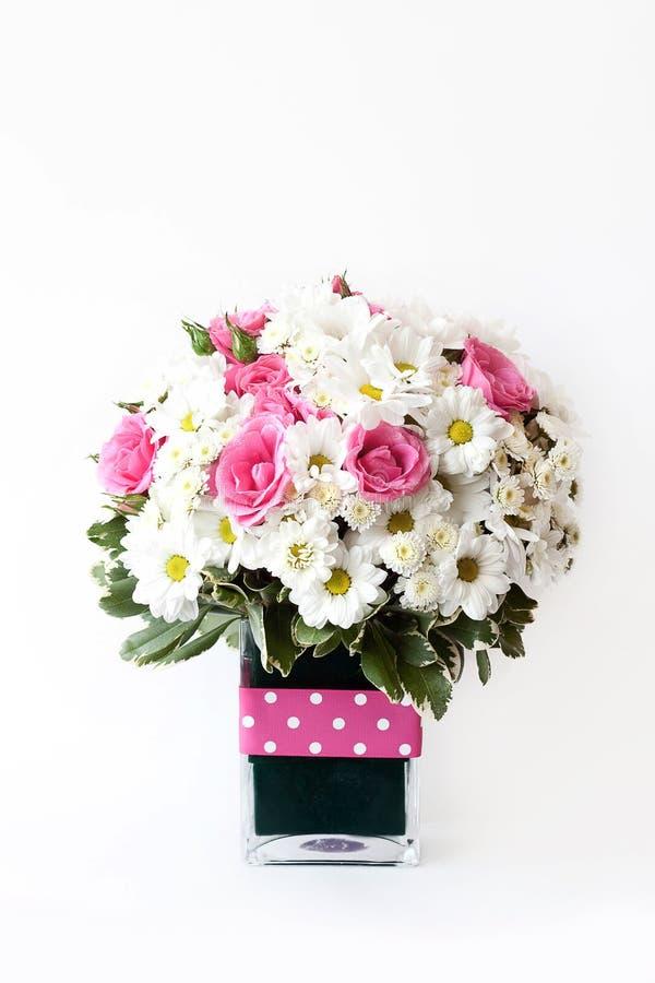 Un ramo modesto de manzanillas y de rosas rosadas en un florero, un regalo a una mujer, primavera y verano imágenes de archivo libres de regalías