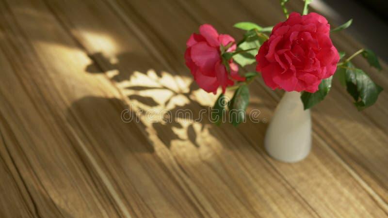 Un ramo precioso de rosas y de fresia y la sombra de ella en la tabla, encendida por la luz del sol a trav?s de la cortina imagen de archivo libre de regalías