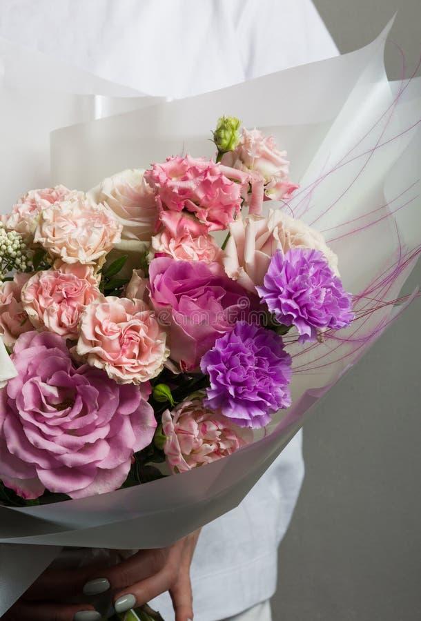 Un ramo que se casa hermoso de las flores, rosas frescas de diversos colores, en las manos de una muchacha imágenes de archivo libres de regalías