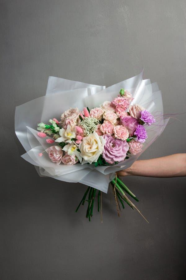Un ramo que se casa hermoso de las flores, rosas frescas de diversos colores, en las manos de una muchacha imagenes de archivo