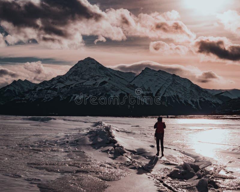 Un randonneur congelé de lac dans le coucher du soleil photo libre de droits