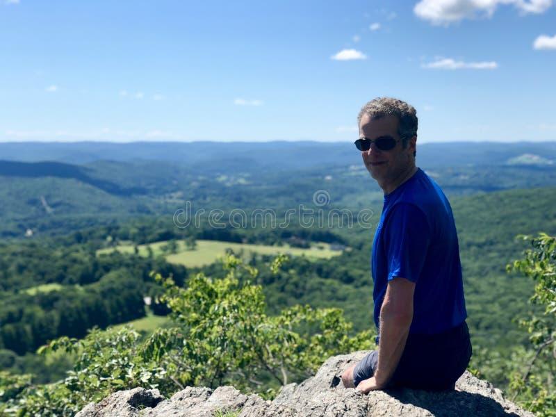 Un randonneur d'homme s'asseyant sur le randonneur d'homme de la montagne A s'asseyant sur la montagne images stock