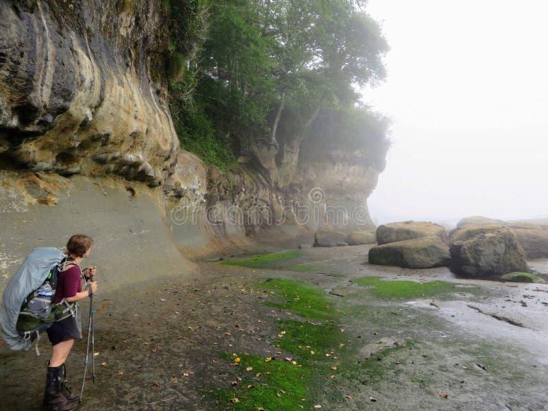 Un randonneur féminin dirigeant soigneusement la ligne de côte le long de la traînée de côte ouest photographie stock